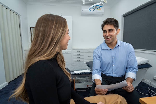 The handsome Dr Django Nathan consulting with a lovely young lady with long hair at Medical Injecatbles in Wollongong and Orange, NSW